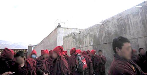 Monniken en leken houden een zwijgende wake buiten de Nangchen gevangenis.