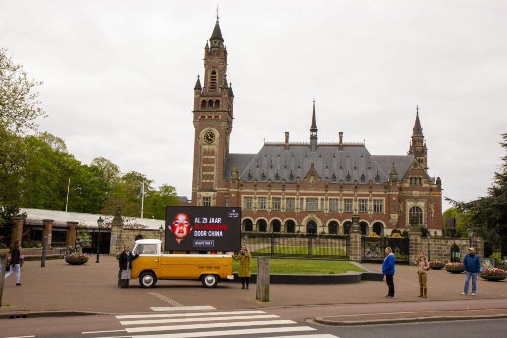 Banner: 'Al 25 jaar in lockdown door China' voor het Vredespaleis in Den Haag
