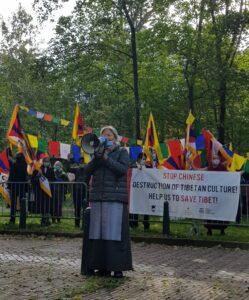 Tsering Jampa voor de Chinese ambassade in Den Haag, met Tibet-supporters en gebedsvlaggen op de achtergrond